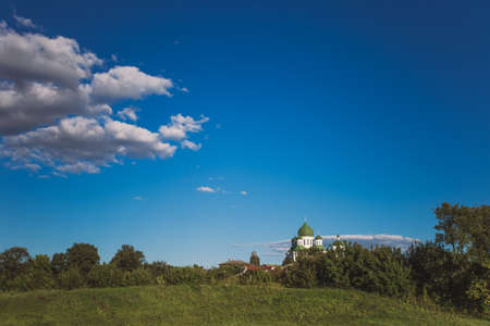 Countryside summer landscape with green meadow, bright blue sky and tops of old church far away in distance. Horizontal color photography.