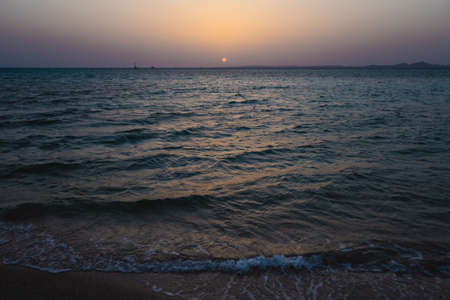 Beautiful sea water and blue sky during sunset or sunrise at sandy tropical beach. Horizontal color photography.