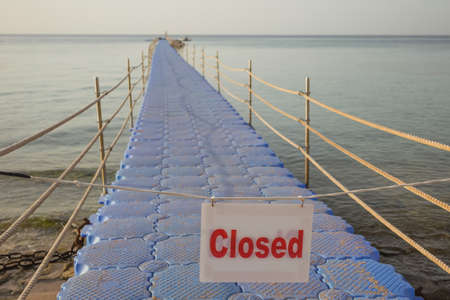 Closed passage to swimming area on summer tropical beach. Horizontal color photography.