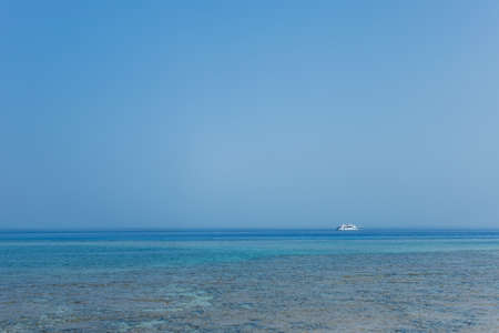 White ship in distance. Blue marine water and clear sky background. Horizontal color photography.