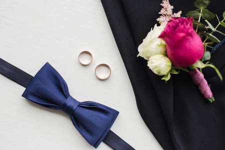 Close up top view of elegant modern formal male accessories. Blue bowtie, two golden wedding rings, flower boutonniere pinned to black jacket of suit. Set for wedding isolated on white background. Standard-Bild