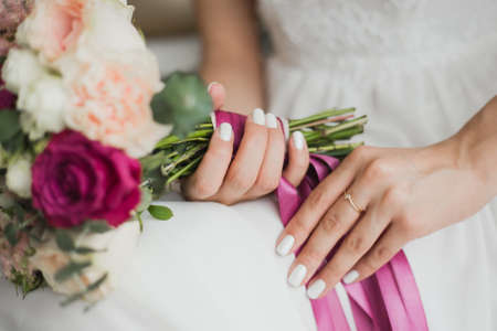 Beautiful colorful wedding flowers in hands of young bride sitting alone in home interior. Fingernails with beautiful bridal manicure and engagement ring. Horizontal color photography.