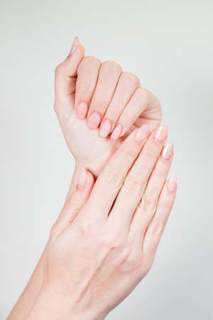 Closeup of two female white hands with old gel polished manicure need correction after several weeks wearing. Vertical color photography. Reklamní fotografie