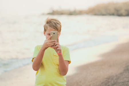 Cute happy smiling white kid using modern smart phone standing at sunset sandy beach of hotel resort in summer. Happy holidays and vacations concept. Horizontal color photography.
