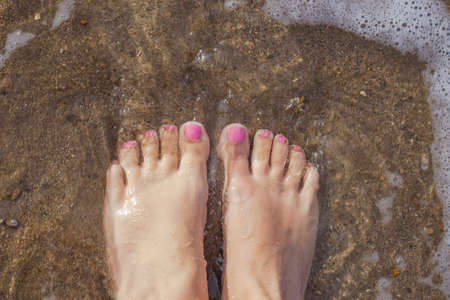 Top view photography of beautiful female barefeet legs with professional pink painted toenails. Pink color pedicure. White tanned woman standing and relaxing on sandy beach at seashore on summer day. 免版税图像