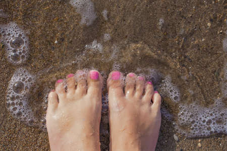 Top view photography of beautiful female barefeet legs with professional pink painted toenails. Pink color pedicure. White tanned woman standing and relaxing on sandy beach at seashore on summer day. Stock fotó
