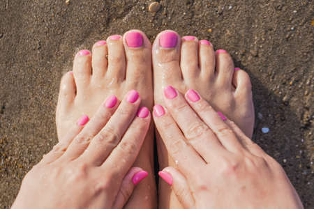 Closeup top view photo of female feet and hands with fresh vibrant pink pedicure and manicure. Woman relaxing at summer sandy beach sitting on seashore near sea water. Horizontal color photography.