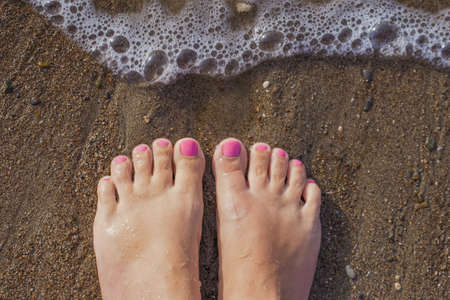 Top view photography of beautiful female barefeet legs with professional pink painted toenails. Pink color pedicure. White tanned woman standing and relaxing on sandy beach at seashore on summer day. Stock Photo