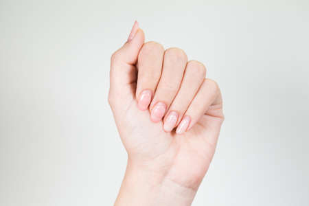 Closeup view of beautiful female hands with old pink manicure. Woman needs correction. Horizontal color photography.