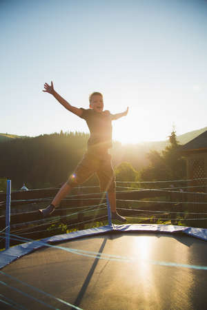 Cute funny cheerful young kid jumping outdoors at trampoline at countryside in soft sunset sunlight. Healthy lifestyle and happy summer vacations concept. Vertical color photography. Standard-Bild
