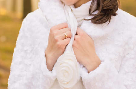 Closeup view of hands of elegant white bride with golden ring at finger. Bride wearing cute scarf and warm coat. Horizontal color photography.