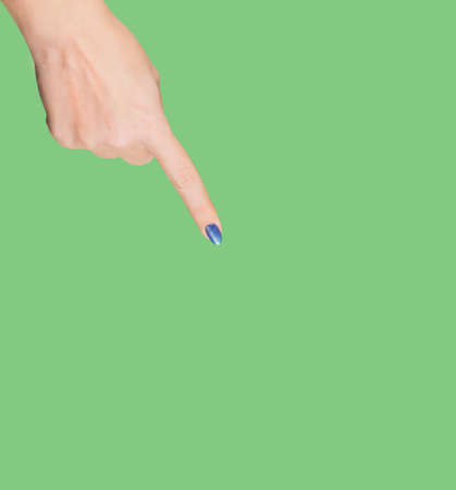 Closeup view of beautiful female hand pointing with her index finger at something virtual and invisible isolated on green background. Square color photography.