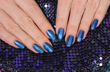 Closeup view of beautiful female hands with blue glossy professional manicure isolated on sparkling holiday background. Horizontal color photography.