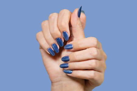 Closeup view of beautiful female hands with blue glossy professional manicure with cat eye effect. Horizontal color photography.