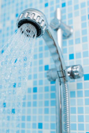 offset angle: Working head shower on blue background Stock Photo