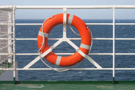 ferrying: Orange life-ring on vessel cruising the sea