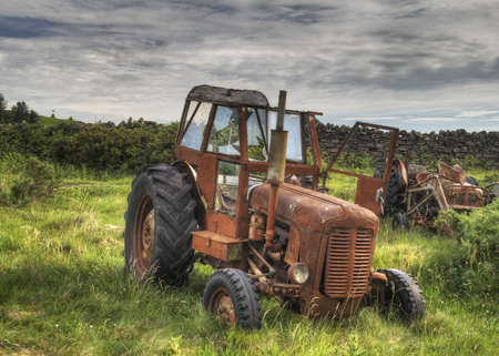 old tractor: Old red rusty tractor in green field Stock Photo