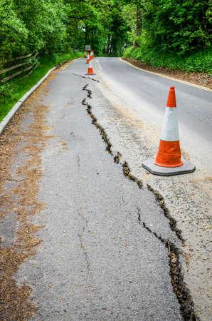 Wegwerkzaamheden op gebarsten asfalt van verzakkingen Stockfoto