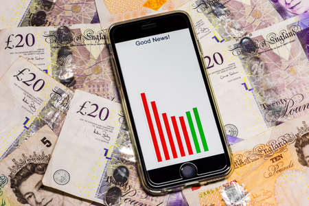 Modern mobile smart phone laying on British tender money ?20 ?10 notes with a Good News message and bar chart graph on screen turn around growth reverse decline photo