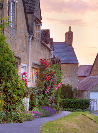 hollyhocks: Cotswold cottages with hollyhocks and roses at sunset, Mickleton near Chipping Campden, Gloucestershire, England  Stock Photo
