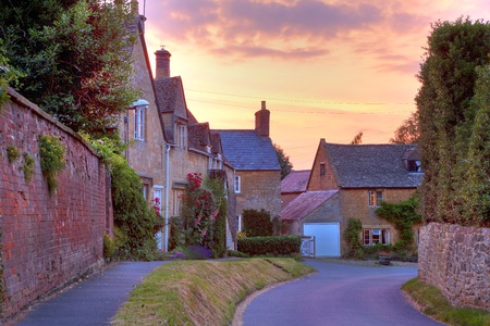 gloucestershire: Cotswold cottages with hollyhocks and roses at sunset, Mickleton near Chipping Campden, Gloucestershire, England  Stock Photo