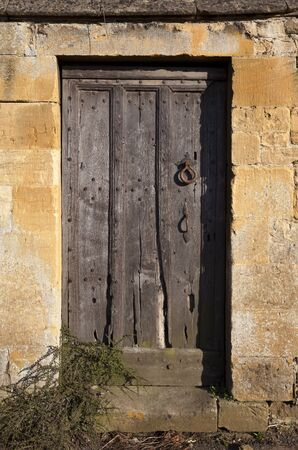 Wooden Cotswold door set into stone wall, Gloucestershire, England  photo