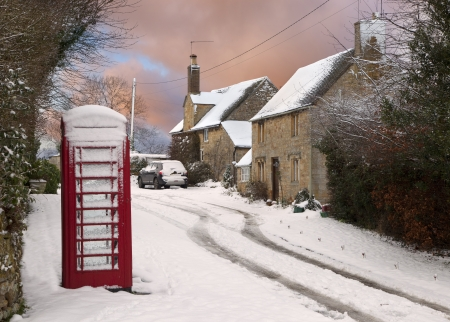 Red phone box and cottages in snow, Cotswolds, Gloucestershire, England  Stockfoto