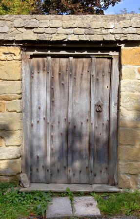 Oak, studded garden gate set into Cotswold stone wall  photo