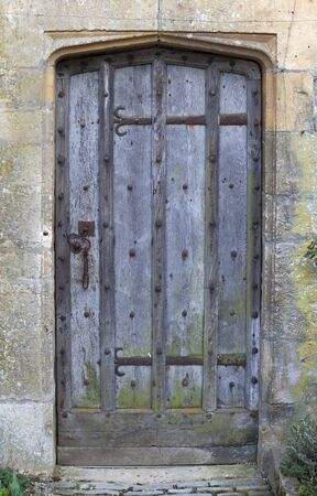 Old studded oak door set into Cotswold stone wall, Gloucestershire, England. photo