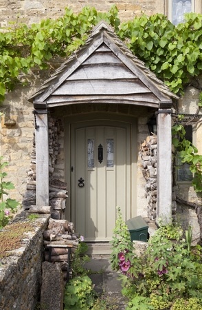 Pretty English cottage doorway with logs and flowers, Cotswolds, Gloucestershire, England. photo