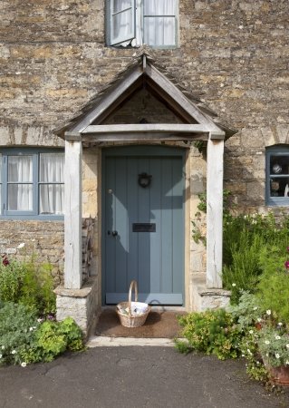 Pretty Cotswold cottage doorway with basket and flowers, Gloucestershire, England. photo
