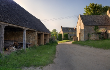 Old traditional English farm at sunset with cart shed and farmhouse