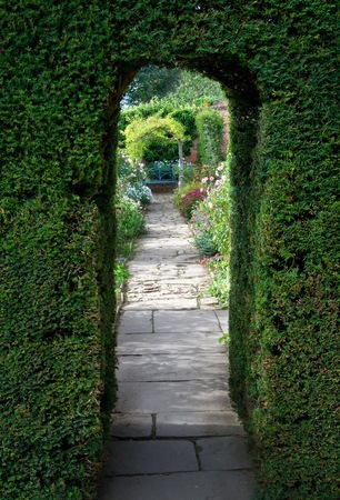 Pretty flagstone path through clipped yew archway towards a bench with flowers, Cotswolds, England.
