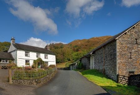 White-washed farmhouse and barns near Loughrigg Tarn, Cumbria, England. photo