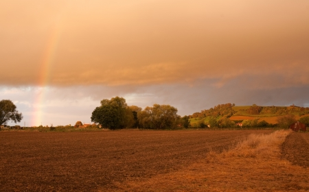 meon: Looking towards Meon Hill over farmland with a dramatic sunset and rainbow, Gloucestershire, England.