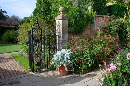 walled: Fine English country garden with fuchias and delphiniums, Gloucestershire, England. Stock Photo