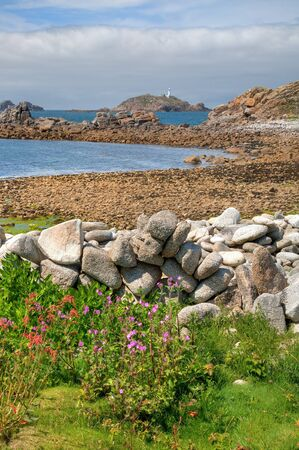 scilly: Looking over a dry-stone wall towards Round Island Lighthouse, St Martin's, Isles of Scilly, Cornwall, England.