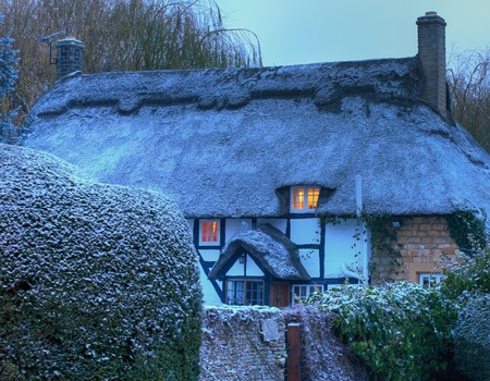 Black and white, timber-framed thatched cottage in winter, Mickleton near Chipping Campden, Gloucestershire, England.