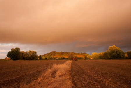 Looking towards Meon Hill over farmland with a dramatic sunset, Gloucestershire, England.