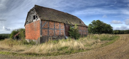 Overgrown timber-frame and brick half-hipped barn, Warwickshire, England.
