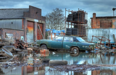 Scrapyard showing flood water and old car, Worcestershire, England.