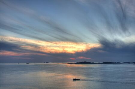 scilly: Lone boat passing Samson island at sunset from St Mary's, Isles of Scilly, Cornwall, England. Stock Photo
