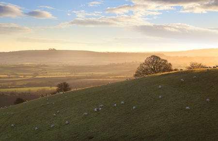 The sun rising a Cotswold landscape near Ilmington, Warwickshire, England