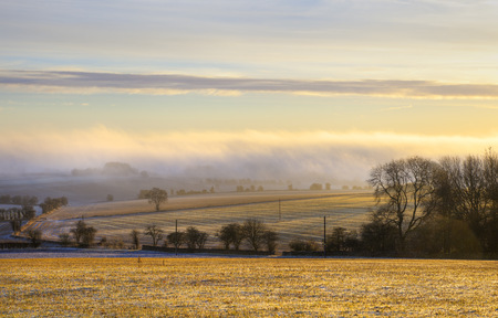 gloucestershire: Cold winters morning with the sun shining through the mist over arable farmland, Gloucestershire, England.