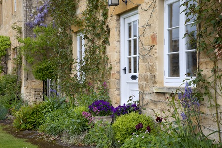 cotswold: Pretty Cotswold cottage with spring-flowering border, Stanton, Gloucestershire, England  Stock Photo