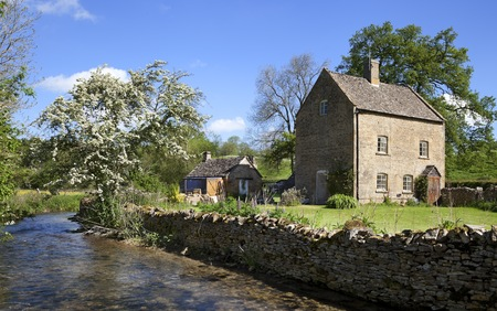 wold: Pretty cottage on the banks of the River Dikler, Gloucestershire, England