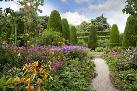 English country garden with clipped yew trees Stockfoto