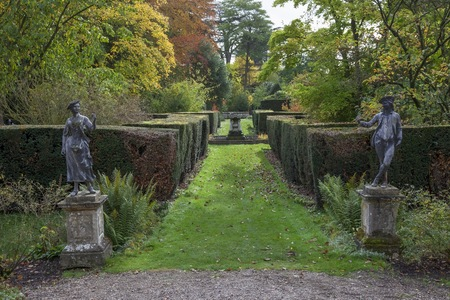 clipped: Country house garden with statues and clipped topiary hedging, Worcestershire, England.
