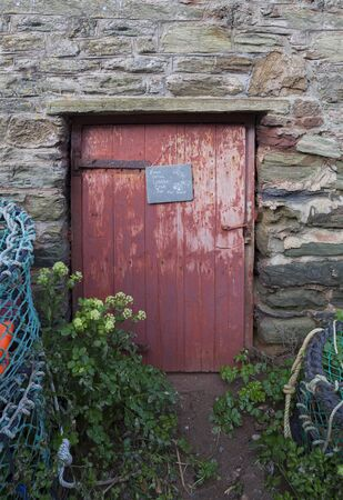 lobster pot: Old door with lobster pots, Devon, England Stock Photo