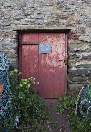 old doors: Old door with lobster pots, Devon, England Stock Photo